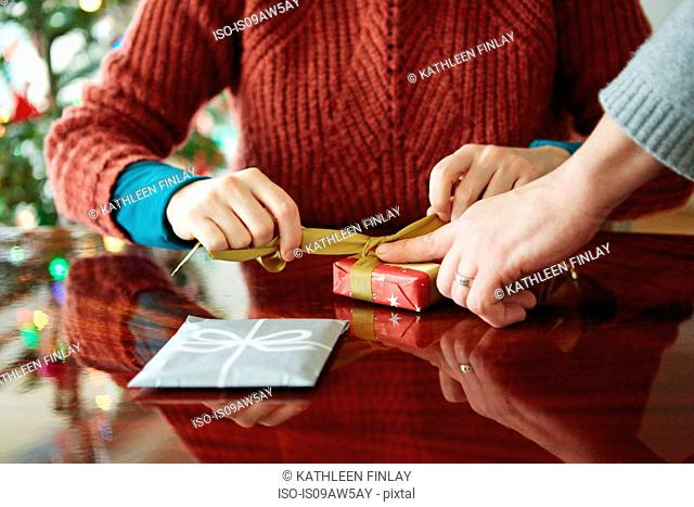 Cropped shot of couples hands wrapping xmas gift at table