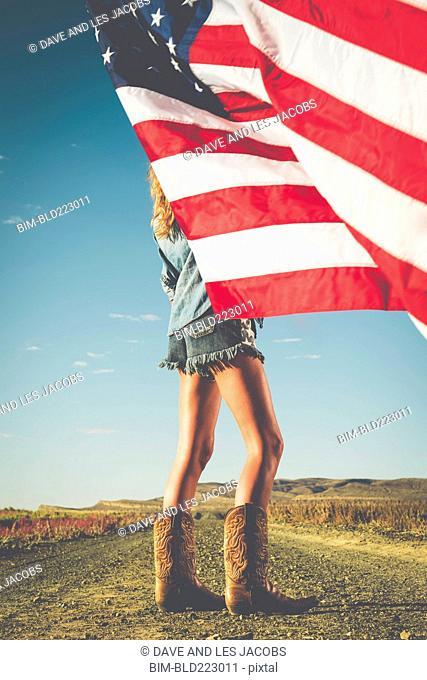 Hispanic woman standing in desert holding American flag