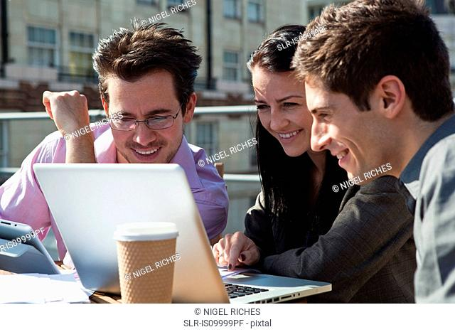 Three people looking at a laptop