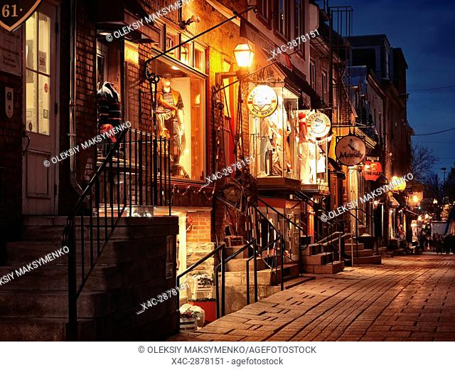 Nighttime view of le Capitaine d'a bord, Mandy and other shops and restaurants on a historic street Rue du Petit Champlain in old Quebec City, Quebec, Canada
