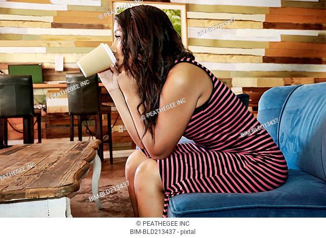 Hispanic woman drinking coffee in cafe