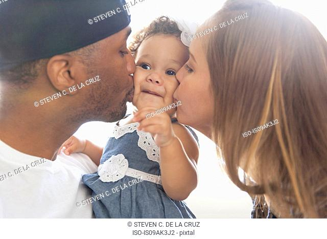Mother and father kissing young daughter on cheeks