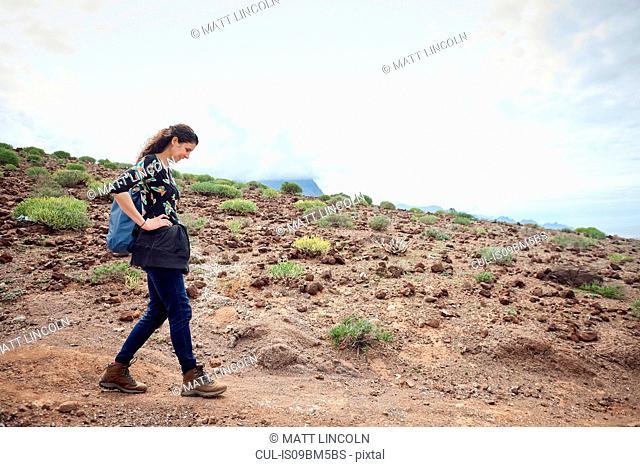 Woman hiking on dirt track in arid landscape, Las Palmas, Gran Canaria, Canary Islands, Spain