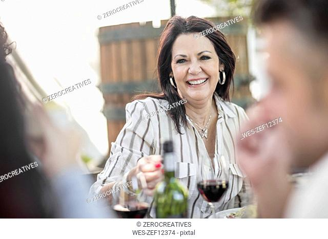 Smiling senior woman at family lunch in garden