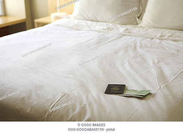 Passport and airplane tickets on made bed