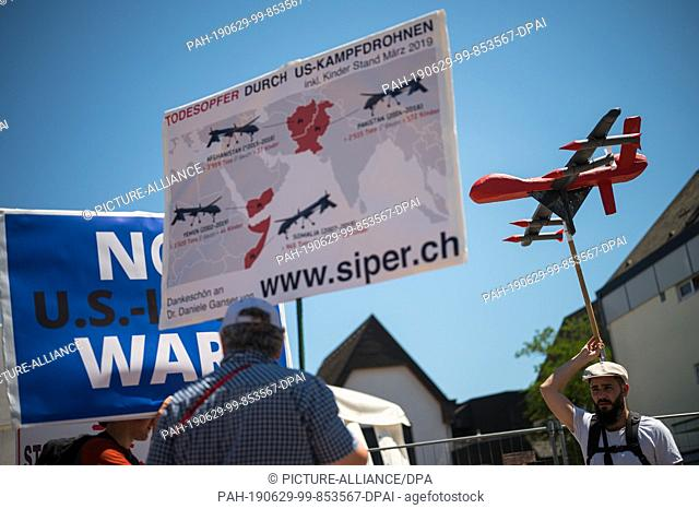 29 June 2019, Rhineland-Palatinate, Ramstein-Miesenbach: A man protests against the use of drones. The peace movement demonstrates against the US Air Base...