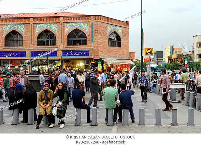Streetscene with people outside of Tehran Bazar and with yellow Metro sign, Tehran, Iran, Asia