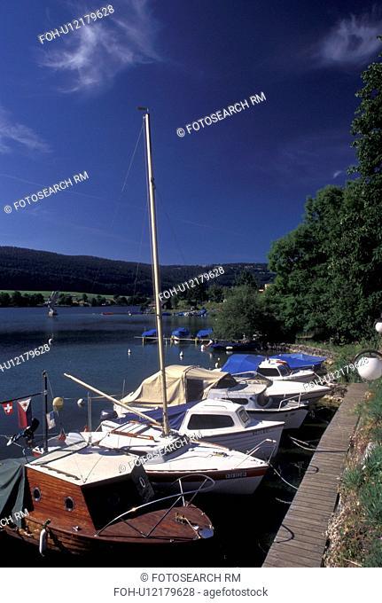 Vallee de Joux, Switzerland, Vaud, Boats docked along the lakefront of Lac de Joux in Le Pont in the Jura mountain region