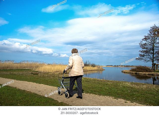 old woman walking with aid at small path alongside a lake in Wormer, Holland