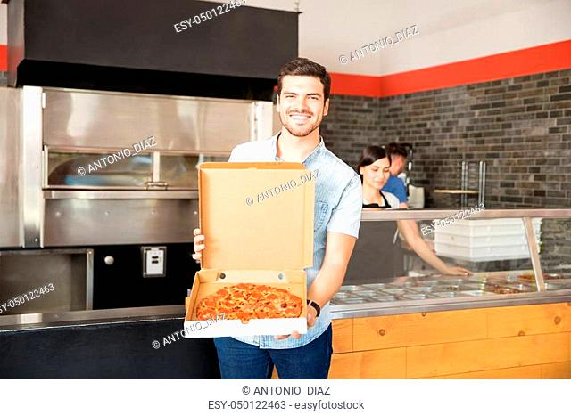 Smiling customer with box showing pizza standing at pizza counter in pizzeria