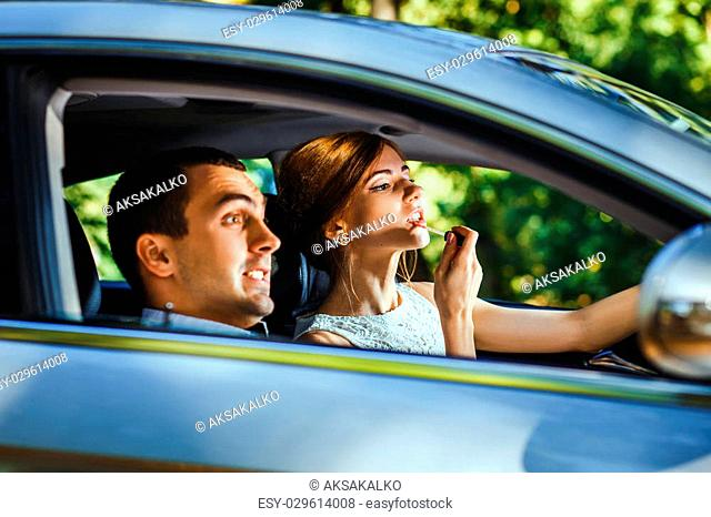 Husband screams until his wife applying lipstick using the rear view mirror in the moving car