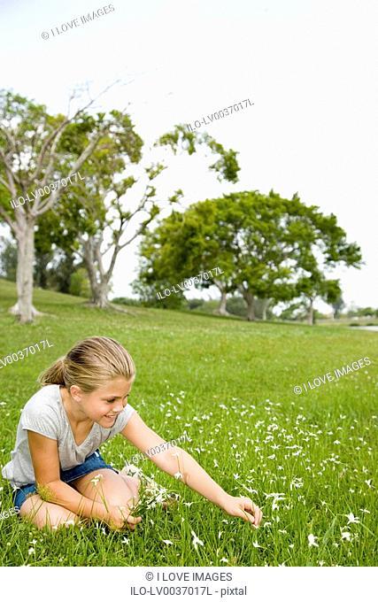 girl sitting on grass picking flowers