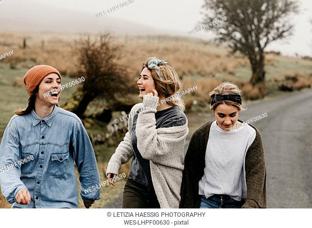 UK, Scotland, Isle of Skye, three happy young woman on a rural road