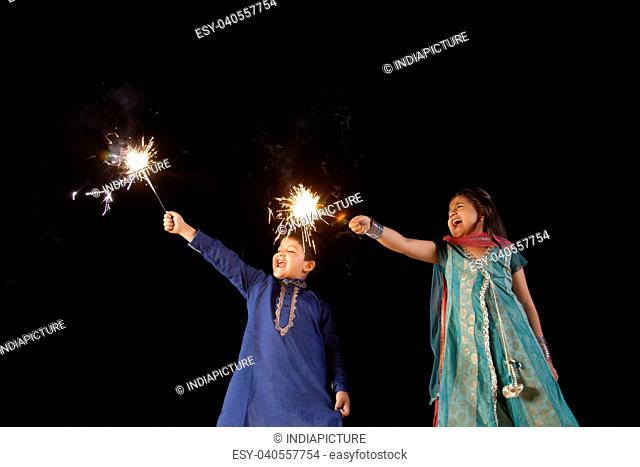Boy and girl playing with sparklers