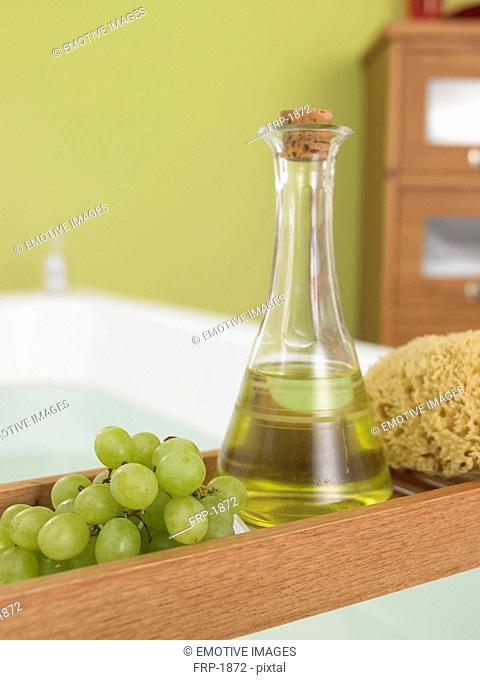 Grapeseed oil and a bunch of grapes on the bathtub tray