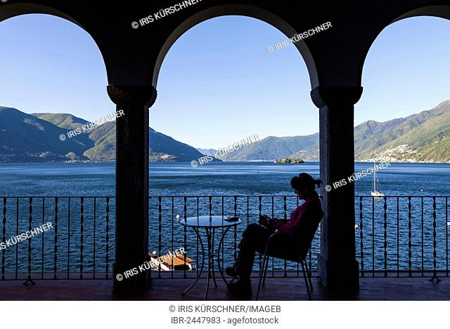 Woman reading under an arcade, view from Casa Moscia, Ascona, Lake Maggiore, Ticino, Switzerland, Europe