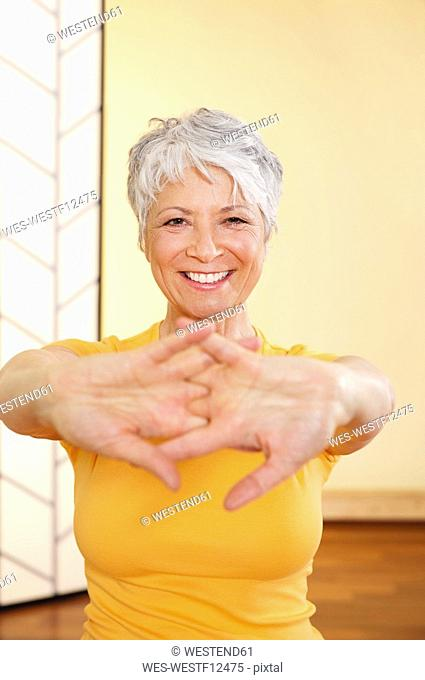 Senor woman stretching hands, smiling, portrait