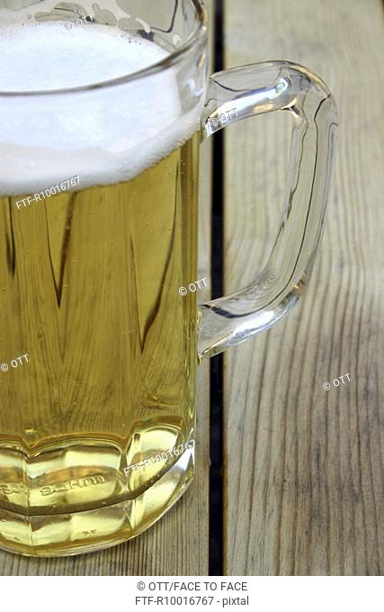 A beer mug is kept on a wooden plank