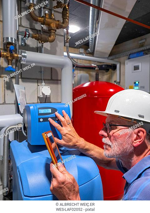 Senior craftsman checking water-processing unit, reading tablet