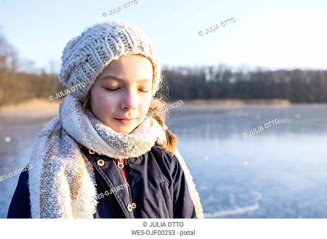 Germany, Brandenburg, Lake Straussee, portrait of a girl standing on frozen lake, eyes closed
