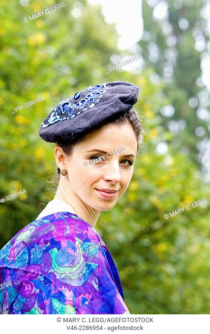 Woman in park with beret and blue scarf. Headshot from side