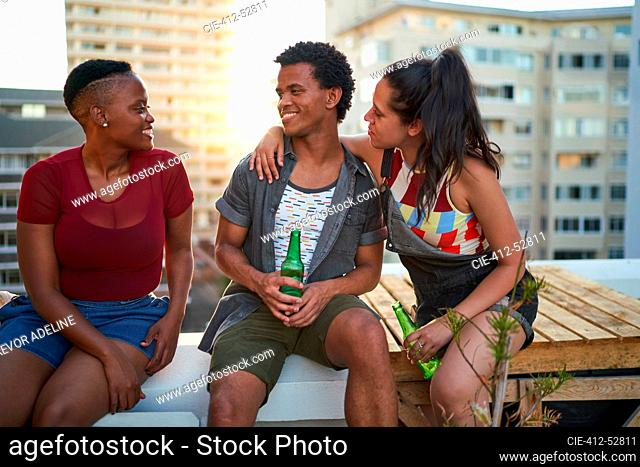 Young friends drinking beer and hanging out on urban rooftop