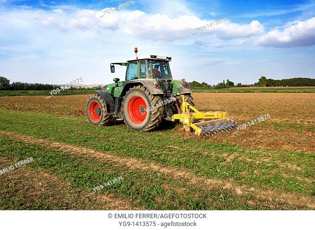 Tractor with machine working on a field  LLeida  Spain