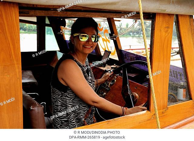 woman driving boat backwater, Munnar, Kerala, India, Asia, MR#802B