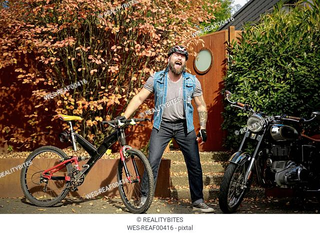 Laughing man standing between motorbike and bicycle