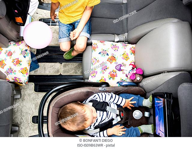 Baby and big brother watching movie in car