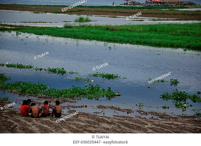 Burmese people sitting talk beside Taungthaman lake at U Bein Bridge