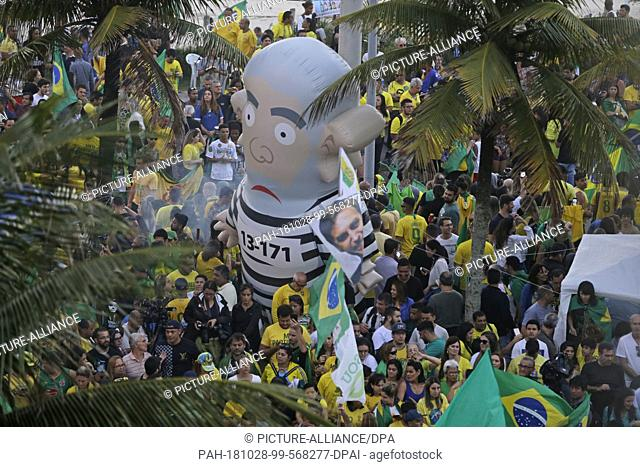 28 October 2018, Brazil, Recife: Supporters of the extreme right-wing presidential candidate Bolsonaro hold a large inflatable figure of Brazil's ex-president...