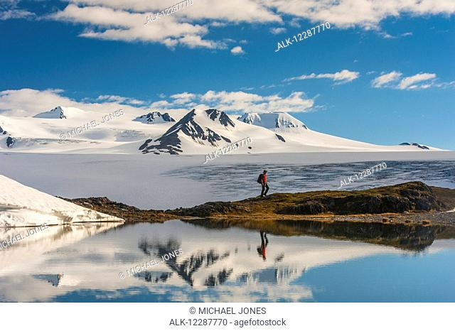 A man hiking by a lake with the Harding Icefield and the Nunatak peaks in the background, Kenai Fjords National Park, Southcentral Alaska