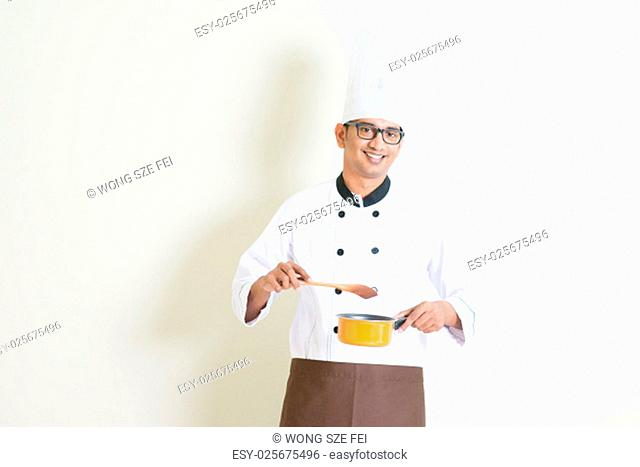 Portrait of handsome Indian male chef in uniform holding cooking pot and stirring food, standing on plain background with shadow, copy space on side