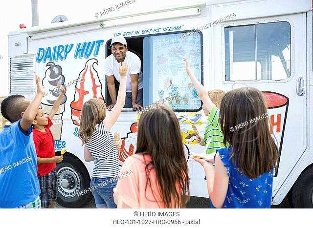 Group of children waving at man in ice cream truck