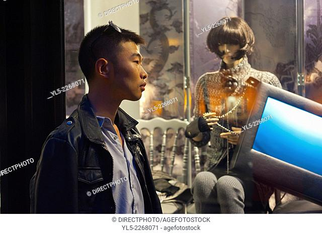 Paris, France, Young Chinese Man Window Shopping, Outside Luxury Shop Window, Night, Avenue Montaigne