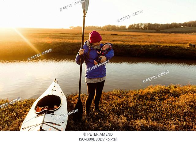 Woman kayaker on riverbank carrying baby daughter at sunset, Morro Bay, California, USA