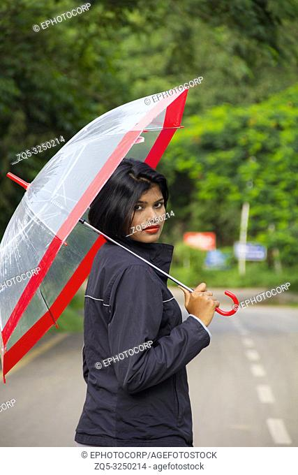 Young Indian girl with short hair holding a transparent umbrella and looking back, Pune