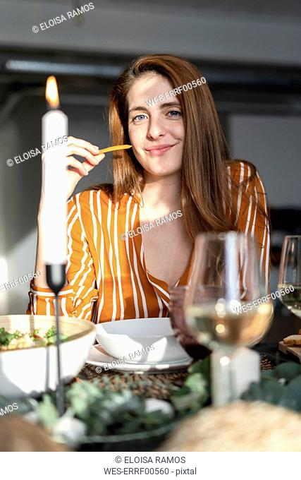 Portrait of a readheaded woman sitting at a dinner party