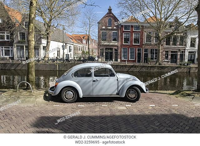 Netherlands, Gouda, 2017, An old volkswagen beetle, parked along the side of a canal or grachten. In the background the typical architecture of the city can be...