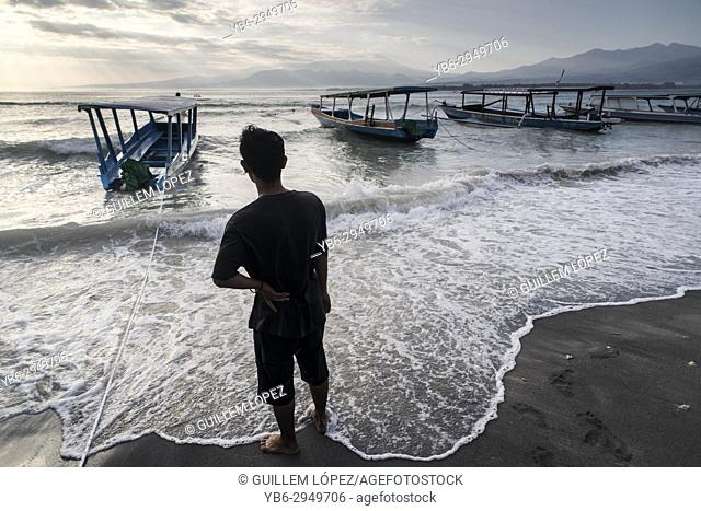 A local men checks his wooden boats during bad weather in Gili Air, Gili Islands, Indonesia