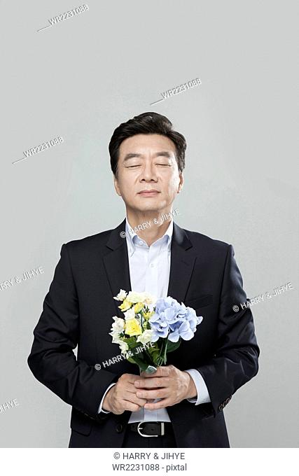 Senior man in suit holding flowers in his hands with his eyes cloed