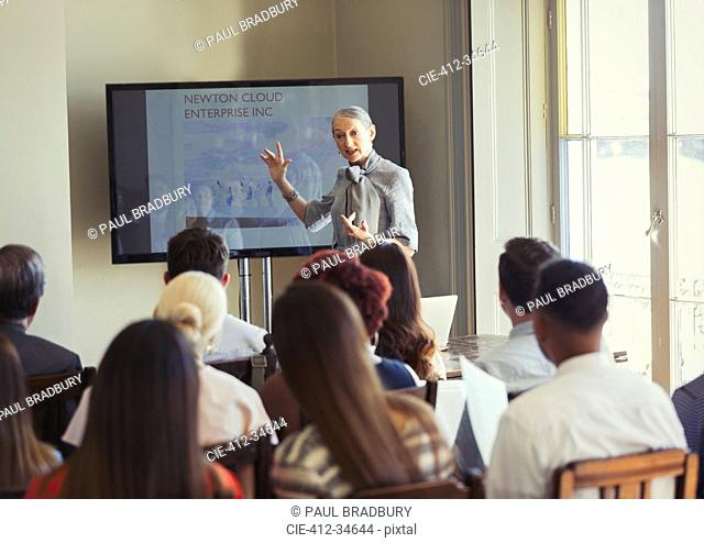 Businesswoman leading conference presentation at television screen