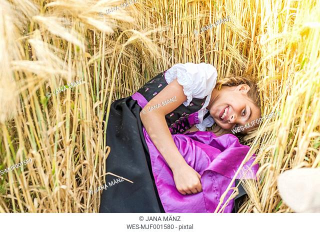 Germany, Saxony, portrait of smiling girl lying in a grain field wearing dirndl