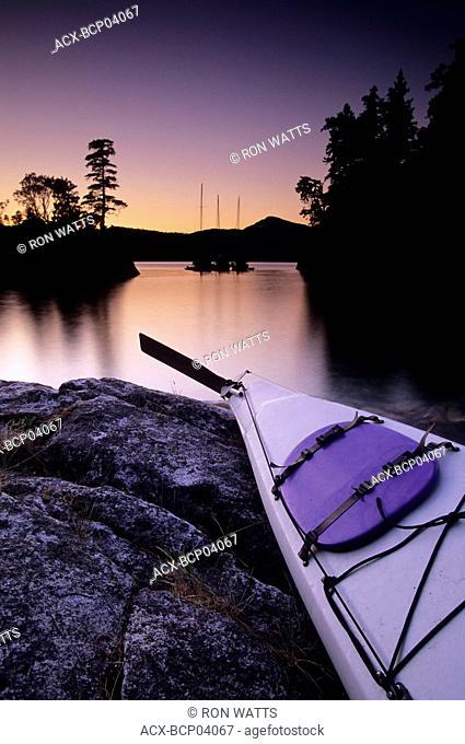 Kayak and Yachts at dusk in Desolation Sound Marine Park, Curme Island, British Columbia, Canada