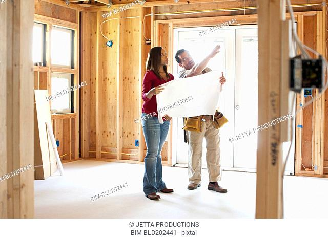 Construction workers looking at blueprints in unfinished room