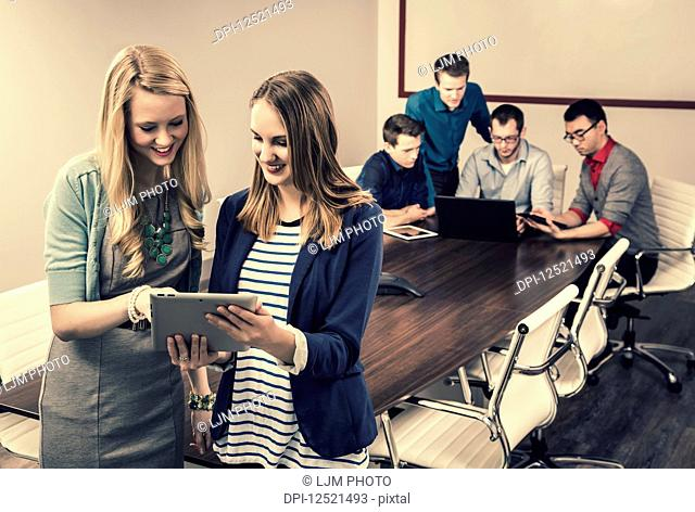 Two young millennial business professionals looking at a pad while working together in a conference room with their piers; Sherwood Park, Alberta, Canada