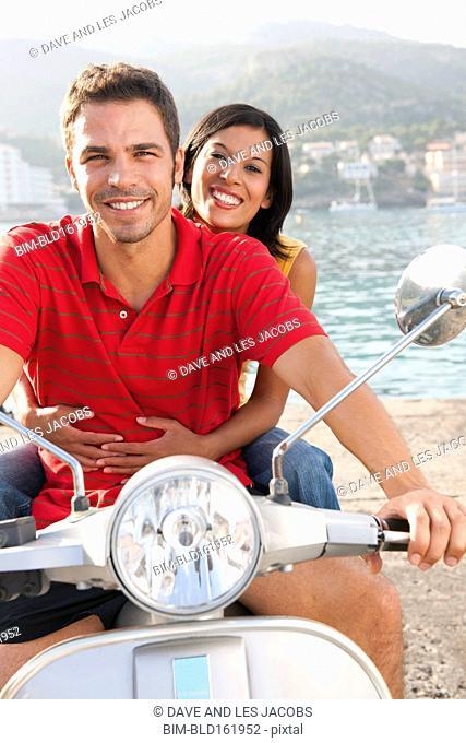 Smiling Hispanic couple riding motor scooter