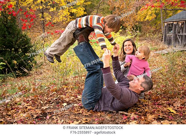Nuclear family with parents in their 30s and with a 3 year old boy and a one year old girl playing on leaf covered lawn in fall