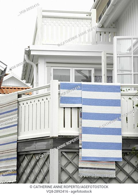 Stripy woven mats hanging out to dry after the rain on the wooden balcony of a harbour side house near Gothenburg, Sweden